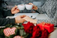 Fond romantique, deux tasses de café et mains des couples dans l Photo stock