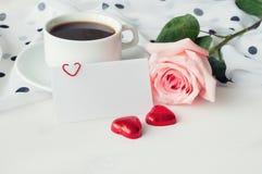 Fond romantique - la tasse de café, s'est levée, masque la carte d'amour et deux sucreries en forme de coeur Image stock