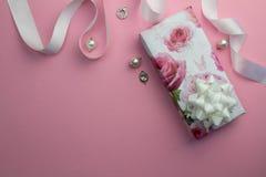 Fond rose avec le cadeau enveloppé, le ruban blanc de satin et la perle Photo libre de droits