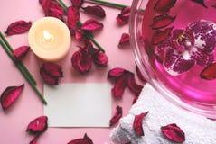 Fond rose avec les pétales, la bougie, la fleur d'orchidée et la cannette de fil secs Photos libres de droits
