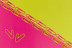 Fond (rose-jaune) bicolore de bureau avec les trombones Photos stock