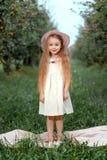 Fond rose rouge d'herbe verte de pommes de cueillette de panier de chapeau d'arbres de jardin de récolte de fille photos libres de droits