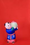 Fond rouge avec la petite figurine d'argile Photos stock