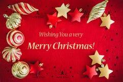 Fond rouge de carte de Noël avec les décorations d'or, les boules et les étoiles, et souhaiter le texte images stock