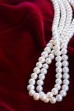 Fond rouge de velours avec des perles Images libres de droits