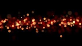 Fond rougeoyant brillant de particules de lumière de Bokeh