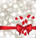 Fond rougeoyant de Noël avec l'arc de cadeau et les cannes douces