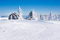 Fond rural d'hiver de vacances avec la petite maison alpine en bois, pins blancs, barrière, champ de neige, montagnes photo libre de droits