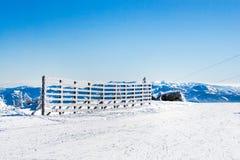 Fond rural d'hiver de vacances avec les pins blancs, barrière, champ de neige, montagnes photo stock
