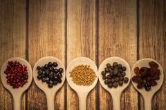 Fond rustique d'agaisnt en bois de cuillères, avec les baies et les graines colorées Photo stock