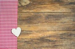 Fond rustique d'amour, coeur en bois sur le tissu à carreaux rouge Photos stock