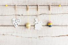 Fond rustique de Pâques : Le coeur et le lapin blancs peints par vintage d'oeufs accrochent sur des pinces à linge contre le vieu Images stock