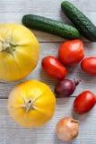 Fond sain de nourriture Différents légumes frais sur un Tableau blanc en bois Tomates, courgette, aubergine, oignon dessus Photos libres de droits
