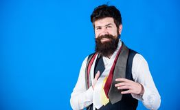 He is fond of shopping. Happy shop assistant offering wide choice of neckties for shopping. Bearded shopper choosing. Necktie in shopping mall. Hipster shopping royalty free stock image