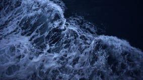 Fond supérieur de vue aérienne de mouvement lent d'écoulement d'impact de mer de ressac la nuit banque de vidéos