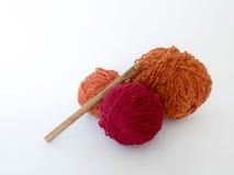 Fond sur la couture avec le crochet de crochet et les boules de la laine Images stock
