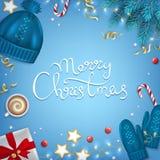 Fond tiré par la main de salutation de lettrage de Joyeux Noël Le sapin d'éléments d'hiver s'embranche, chapeau bleu tricoté, mit Photos stock