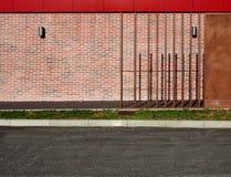 Fond urbain Mur de briques, avec les panneaux rouges et bruns en métal autour de lui, de l'herbe verte et d'une route bétonnée Image libre de droits