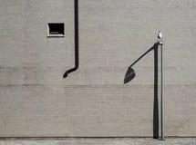 Fond urbain Mur extérieur fait de carreaux de céramique avec un réverbère et son ombre Photos libres de droits