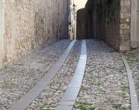 Fond urbain Route médiévale faite de pavés ronds et dalles de granit entre les bâtiments antiques Images stock