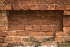 Fond urbain sale d'un mur de briques avec une vieille cabine téléphonique hors service Images stock