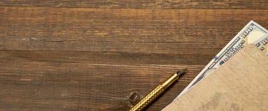 Fond vide en bois avec le carnet, l'argent et le stylo d'or Images stock