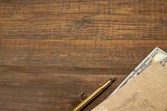 Fond vide en bois avec le carnet, l'argent et le stylo d'or Photos stock