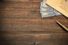 Fond vide en bois avec le carnet, l'argent et le stylo d'or Photographie stock libre de droits