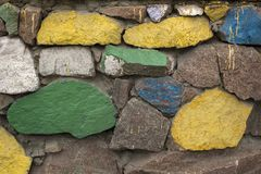 Fondamento ma pietre dipinti nei colori differenti Fine della parete delle macerie della costruzione su immagini stock