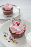 Fondant butterfly cupcakes. Pink butterfly cupcakes with white butterflies on floral plate Royalty Free Stock Image