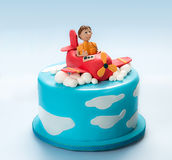 Fondant Cake of an airplane and pilot. Artistic fondant cake decorated on top with airplane and the happy pilot over clouds Royalty Free Stock Photography