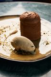Fondant cake Dessert and pistachio ice cream with English cream. Pistachio crumble and sauce bailies stock image