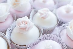 Fondant covered cupcakes with edible roses on top. stock photo