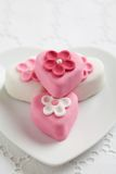Fondant-covered petit fours on herat shaped plate Royalty Free Stock Photography