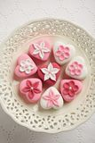 Fondant-covered petit fours on vintage style cake stand Stock Image