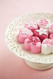 Fondant-covered petit fours on vintage style cake stand Stock Photo