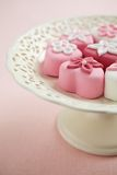 Fondant-covered petit fours on vintage style cake stand Royalty Free Stock Image