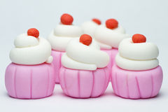 Fondant cupcakes. On a plain background royalty free stock image