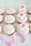 Fondant cupcakes on wooden table. Delicate fondant rose cupcake with pink ribbon Royalty Free Stock Images