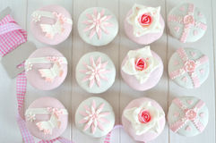 Fondant cupcakes on wooden table with ribbon. Delicate fondant cupcakes with pink ribbon on white wooden table Stock Image