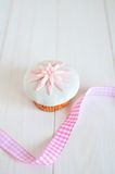 Fondant daisy cupcake. Delicate fondant daisy cupcake with pink ribbon on white wooden table Stock Photo