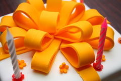 Fondant Gift Cake. A fondant-covered orange-colored cake in the shape of a gift stock photo