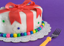 Fondant Gift Cake With Fork. A fondant-covered cake in the shape of a gift sits on purple with a fork ready to stab into it Royalty Free Stock Image