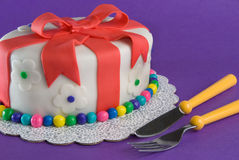 Fondant Gift Cake With Fork and Knife. A fondant-covered cake in the shape of a gift sits on purple with a fork and knife ready to stab into it Royalty Free Stock Photos