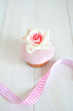 Fondant rose cupcake. Delicate fondant rose cupcake with pink ribbon Royalty Free Stock Photography