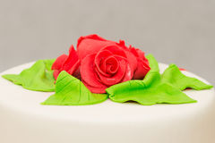 Fondant roses. Fondant covered cake with red sugar roses royalty free stock photo