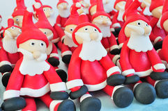 Fondant Santas. Santa Clause made of fondant sitting together Stock Image