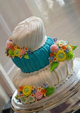 Fondant wedding cake. Blue and white fondant wedding cake with colorful floral decoration royalty free stock photography