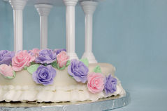 Fondant Wedding Cake. A fondant-covered two-tier wedding cake covered in icing flowers royalty free stock photography