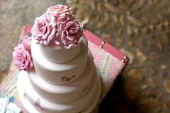 Fondant wedding cake. With pink roses over vintage suitcase stock images